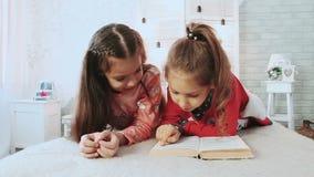 Δύο μικροί φίλοι, είναι στις πυτζάμες και αυτοί βιβλίο ανάγνωσης Μιλούν και συζητούν το βιβλίο απόθεμα βίντεο