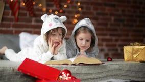 Δύο μικροί χαριτωμένοι αμφιθαλείς που διαβάζουν ένα βιβλίο στο κρεβάτι κοντά στο χριστουγεννιάτικο δέντρο με τα φω'τα και το φωτι φιλμ μικρού μήκους