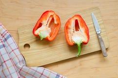 Δύο μισά του κόκκινου πιπεριού στον πίνακα κουζινών Στοκ φωτογραφία με δικαίωμα ελεύθερης χρήσης
