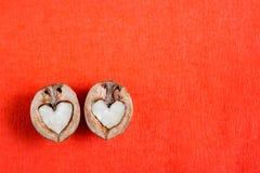 Δύο μισά του ξύλου καρυδιάς στη μορφή της καρδιάς βρίσκονται κόκκινο σε κατασκευασμένο Στοκ Φωτογραφία