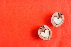 Δύο μισά του ξύλου καρυδιάς στη μορφή της καρδιάς βρίσκονται κόκκινο σε κατασκευασμένο Στοκ Εικόνα