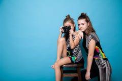 Δύο μοντέρνα κορίτσια που θέτουν με μια κάμερα σε ένα μπλε υπόβαθρο Στοκ φωτογραφία με δικαίωμα ελεύθερης χρήσης
