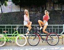 Δύο μοντέρνα νέα και προκλητικά κορίτσια στα ποδήλατα το καλοκαίρι Στοκ Εικόνες