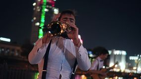 Δύο μουσικοί οδών, ένα saxophonist και ένας κιθαρίστας παίζουν στο ανάχωμα της πόλης νύχτας Όμορφο τοπίο βραδιού φιλμ μικρού μήκους