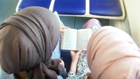 Δύο μουσουλμανικές γυναίκες διαβάζουν ένα βιβλίο στο τραίνο απόθεμα βίντεο