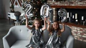 Δύο μπαλόνια του νέου έτους χεριών εκμετάλλευσης μικρών κοριτσιών χαμόγελου, Αριθμός 2019 στενός κόκκινος χρόνος Χριστουγέννων αν φιλμ μικρού μήκους