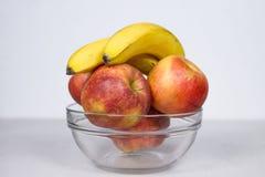 Δύο μπανάνες και τέσσερα μήλα στην απομονωμένη κύπελλο σύνθεση γυαλιού στο άσπρο υπόβαθρο στοκ εικόνα