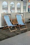 Δύο μπλε και λευκό που γδύνεται deckchairs στην αποβάθρα του Μπράιτον Στοκ Φωτογραφίες