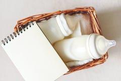 Δύο μπουκάλια με το μητρικό γάλα για το μωρό σε ένα σημειωματάριο καλαθιών και εγγράφου αχύρου κοντά σε το Ελεύθερο διάστημα αντι Στοκ φωτογραφίες με δικαίωμα ελεύθερης χρήσης