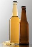 Δύο μπουκάλια της μπύρας και των τσιπ Στοκ Εικόνες
