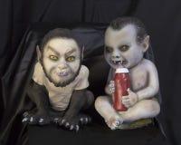 Δύο μωρά ένα τεράτων που πίνουν ένα σύνολο μπουκαλιών του αίματος Στοκ Εικόνες