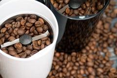Δύο μύλοι καφέ με τα φασόλια καφέ στους ξύλινους πίνακες στοκ φωτογραφία