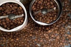 Δύο μύλοι καφέ με τα φασόλια καφέ στους ξύλινους πίνακες στοκ εικόνα