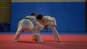 Δύο νέα αγόρια έντυσαν στα άσπρα karate κιμονό παίζοντας με ένα γάντι στο dojo απόθεμα βίντεο