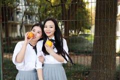 Δύο νέα ασιατικά κινεζικά όμορφα κορίτσια φορούν το κοστούμι σπουδαστών στα πορτοκαλιά φρούτα μυρωδιάς γέλιου χαμόγελου σχολικών  στοκ φωτογραφία με δικαίωμα ελεύθερης χρήσης