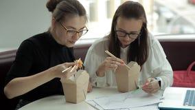 Δύο νέα επιχειρησιακά κορίτσια κάθονται σε έναν καφέ, τρώνε τα κινεζικά νουντλς και συζητούν τη ανάπτυξη επιχείρησης εργασία Κατα απόθεμα βίντεο