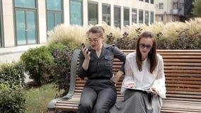 Δύο νέα επιχειρησιακά κορίτσια κάθονται στο πάρκο κοντά στο εμπορικό κέντρο και περιμένουν ένα τηλεφώνημα Τηλεφώνημα απόθεμα βίντεο