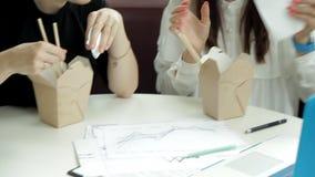 Δύο νέα επιχειρησιακά κορίτσια με τα γυαλιά που κάθονται σε έναν καφέ σε ένα lap-top, που τρώνε τα κινεζικά νουντλς και που εξετά απόθεμα βίντεο