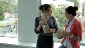Δύο νέα επιχειρησιακά κορίτσια που εργάζονται σε μια τράπεζα και ένα μεσημεριανό γεύμα στο παράθυρο που τρώει τα κινεζικά νουντλς απόθεμα βίντεο