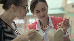Δύο νέα επιχειρησιακά κορίτσια που εργάζονται σε μια τράπεζα και ένα μεσημεριανό γεύμα στο παράθυρο που τρώει τα κινεζικά νουντλς φιλμ μικρού μήκους