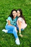 Δύο νέα ευτυχή κορίτσια βρίσκονται στη χλόη Στοκ Φωτογραφίες