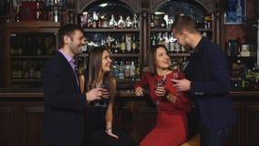 Δύο νέα ζεύγη στο κλαμπ ή το μπαρ που έχει τη διασκέδαση, ψήνοντας τα γυαλιά κρασιού φιλμ μικρού μήκους