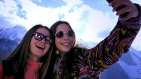 Δύο νέα κορίτσια αναρριχούνται στα βουνά, κάνουν selfie τα βουνά στο υπόβαθρο, χαμόγελο Απολαύστε το χειμερινό βουνό φιλμ μικρού μήκους