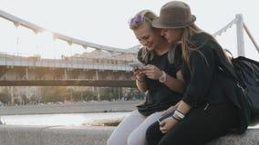 Δύο νέα κορίτσια εφήβων κάθονται στο ανάχωμα και χρησιμοποιούν το τηλέφωνό τους φιλμ μικρού μήκους