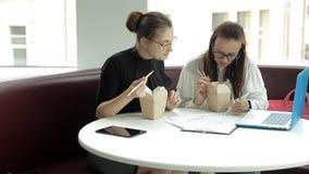 Δύο νέα κορίτσια κάθονται σε έναν καφέ σε ένα lap-top, τρώνε τα κινεζικά νουντλς και συζητούν τη ανάπτυξη επιχείρησης απόθεμα βίντεο