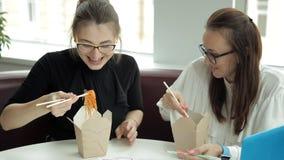 Δύο νέα κορίτσια κάθονται σε έναν καφέ, τρώνε τα κινεζικά νουντλς και προγραμματίζουν τη ανάπτυξη επιχείρησης απόθεμα βίντεο