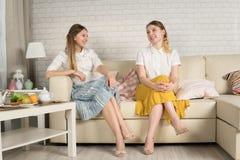 Δύο νέα κορίτσια κάθονται στον καναπέ Στοκ Φωτογραφία