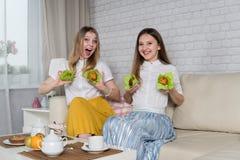 Δύο νέα κορίτσια κάθονται στον καναπέ στοκ εικόνα με δικαίωμα ελεύθερης χρήσης