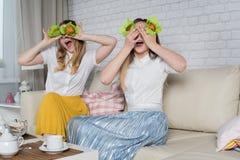 Δύο νέα κορίτσια κάθονται στον καναπέ στοκ φωτογραφίες