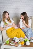 Δύο νέα κορίτσια κάθονται στον καναπέ στοκ εικόνες