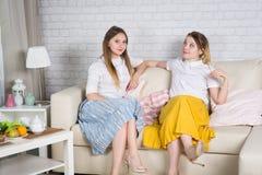 Δύο νέα κορίτσια κάθονται στον καναπέ στοκ φωτογραφίες με δικαίωμα ελεύθερης χρήσης