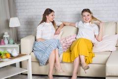 Δύο νέα κορίτσια κάθονται στον καναπέ στοκ φωτογραφία με δικαίωμα ελεύθερης χρήσης