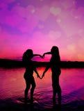 Δύο νέα κορίτσια κάνουν τη μορφή της καρδιάς Στοκ Φωτογραφία