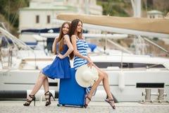 Δύο νέα κορίτσια με μια βαλίτσα σε μια μαρίνα στοκ εικόνες