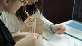 Δύο νέα κορίτσια με τα γυαλιά κάθονται σε έναν καφέ σε ένα lap-top, τρώνε τα κινεζικά νουντλς και συζητούν τη γραφική παράσταση απόθεμα βίντεο