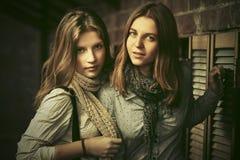 Δύο νέα κορίτσια μόδας δίπλα στο τουβλότοιχο Στοκ Φωτογραφίες