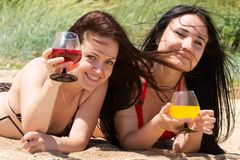 Δύο νέα κορίτσια πίνουν τα κοκτέιλ στην παραλία Στοκ Φωτογραφίες