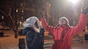 Δύο νέα κορίτσια περπατούν στην πόλη βραδιού στο χειμερινό καιρό φιλμ μικρού μήκους