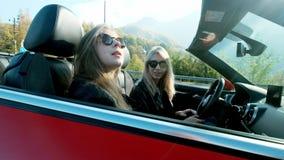 Δύο νέα κορίτσια πηγαίνουν σε ένα καμπριολέ κοντά στα υψηλά βουνά απόθεμα βίντεο
