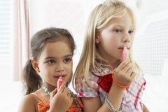Δύο νέα κορίτσια που ντύνουν επάνω και που βάζουν αποτελούν από κοινού Στοκ Φωτογραφία