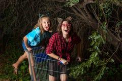 Δύο νέα κορίτσια που παίζουν σε ένα κάρρο αγορών κάτω από με στοκ φωτογραφία με δικαίωμα ελεύθερης χρήσης