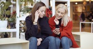 Δύο νέα κορίτσια που χρησιμοποιούν το κινητό τηλέφωνο σε μια πόλη στοκ εικόνα με δικαίωμα ελεύθερης χρήσης