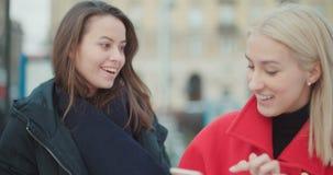 Δύο νέα κορίτσια που χρησιμοποιούν το κινητό τηλέφωνο σε μια πόλη απόθεμα βίντεο