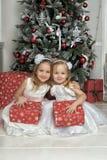 Δύο νέα κορίτσια στα άσπρα φορέματα με τα δώρα Στοκ Φωτογραφίες