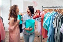Δύο νέα κορίτσια στις αγορές Τα κορίτσια επιλέγουν τα ενδύματα στο κατάστημα Κορίτσια στην αίθουσα εκθέσεως στοκ φωτογραφίες με δικαίωμα ελεύθερης χρήσης