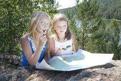 Δύο νέα κορίτσια στο βουνό διαβάζουν το χάρτη πλησίον Στοκ φωτογραφία με δικαίωμα ελεύθερης χρήσης